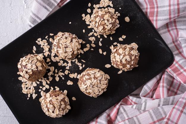 日付、オーツ麦フレーク、乾燥クランベリー、ピーカンナッツ、ブラックプレートで作られた健康的な有機エネルギーボール