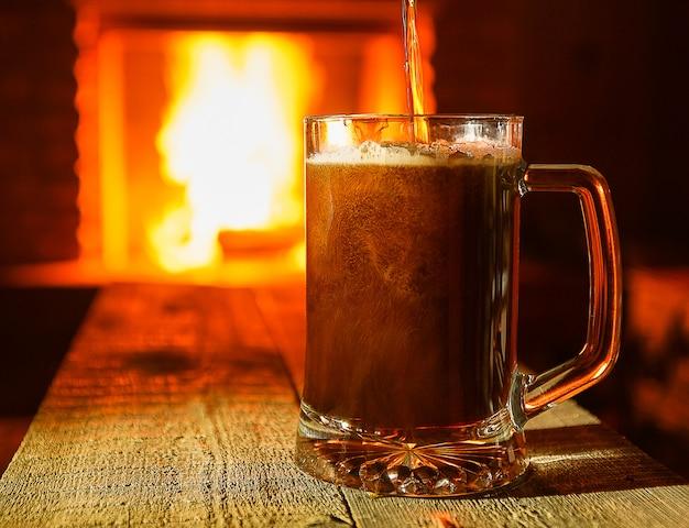 暖炉の背景の近くのマグカップでビール。