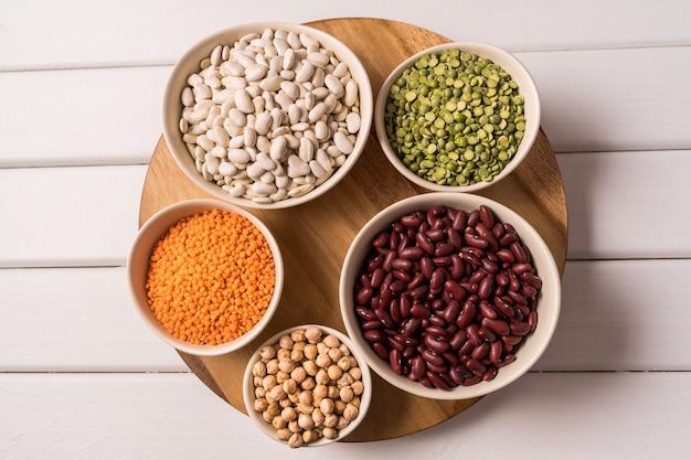 エンドウ豆、レンズ豆、豆、マメ科植物の白い木製の品揃えの平面図です。