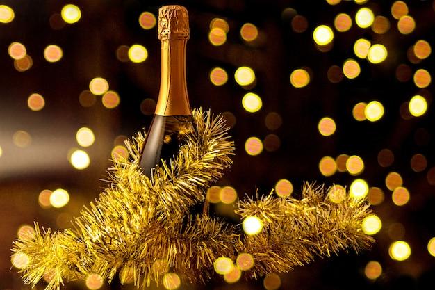 Праздничное рождественское украшение с бутылкой шампанского и блестящим конфетти.