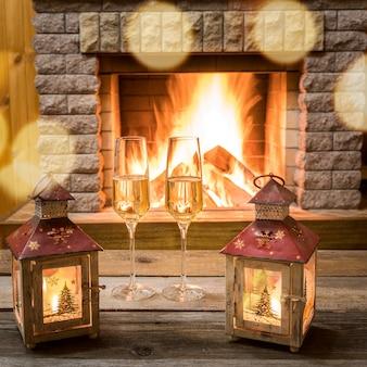 Рождественские фонарики и бокалы для шампанского возле уютного камина, в загородном доме.