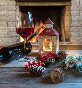Рождественский фонарь, красное вино и рождественские украшения возле уютного камина, в загородном доме.