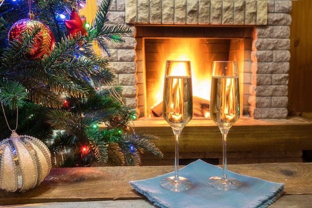 Рождественский сочельник. два бокала шампанского вина возле уютного камина и перед рождественской елкой украшали игрушки и рождественские огни в загородном доме.