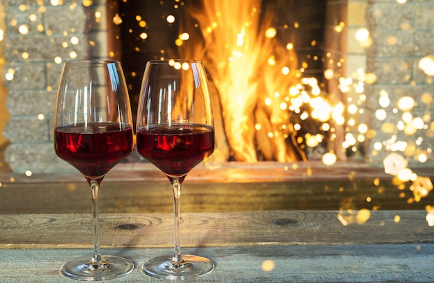Рождество перед уютным камином с бокалами вина и рождественские украшения, в загородном доме.