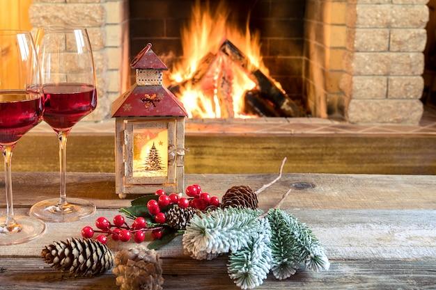 Два бокала вина и рождественский фонарь возле уютного камина, в загородном доме.