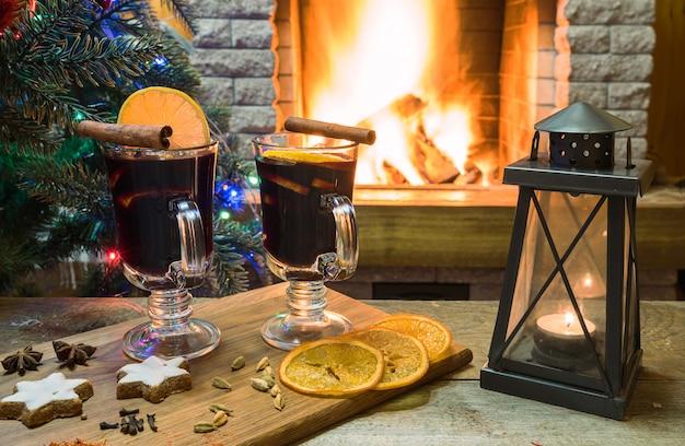 Два бокала глинтвейна на деревянной доске до горения камина и новогодней елки.