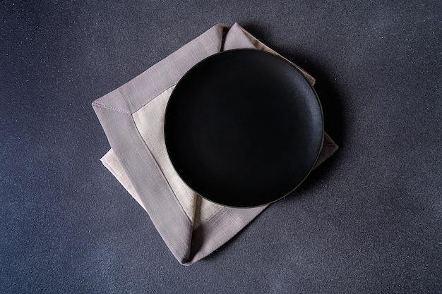 Черная плита с салфеткой на каменном взгляде столешницы. место для меню или рецепта.