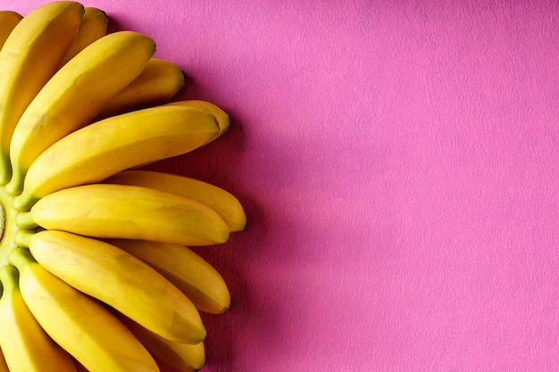 Предпосылка еды с плодоовощ банана на розовой бумаге.