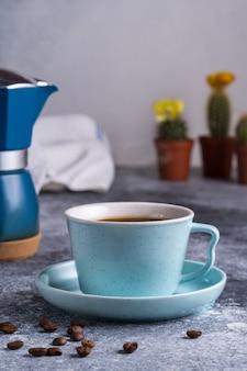 Черный кофе в чашке, гейзерная кофеварка и кофейные зерна на доске