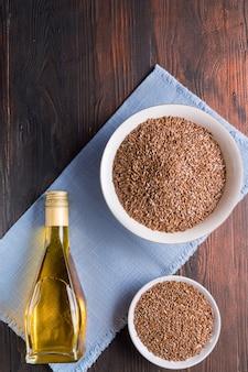 Семена льна коричневого цвета и льняное масло на деревянной поверхности, плоская планировка.