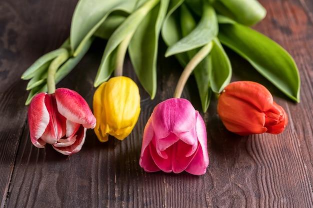 茶色の木製の背景上の春のチューリップの花の花束。