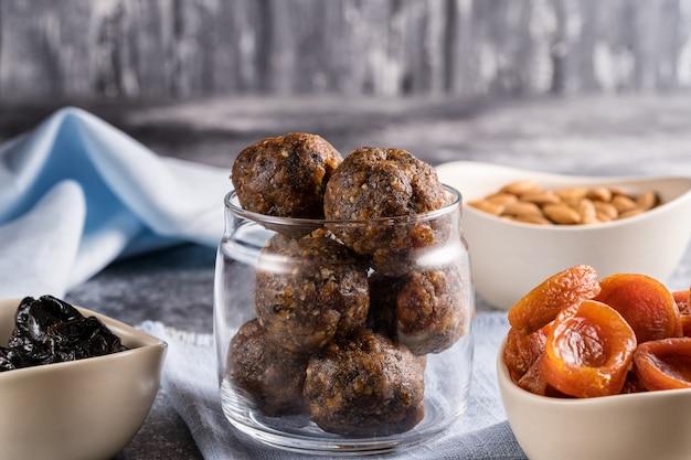 Энергетические шарики из сухофруктов и орехов в стеклянной банке, рядом с ингредиентами для приготовления кураги, чернослива, миндаля.