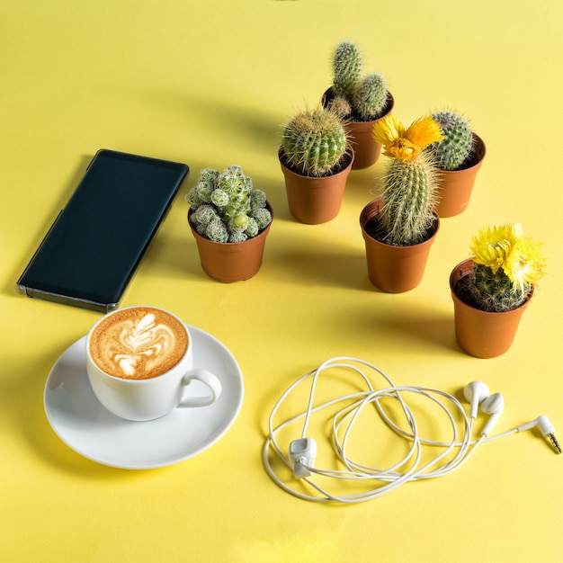 Композиция с чашкой кофе, смартфоном и наушниками, в окружении горшков с кактусами