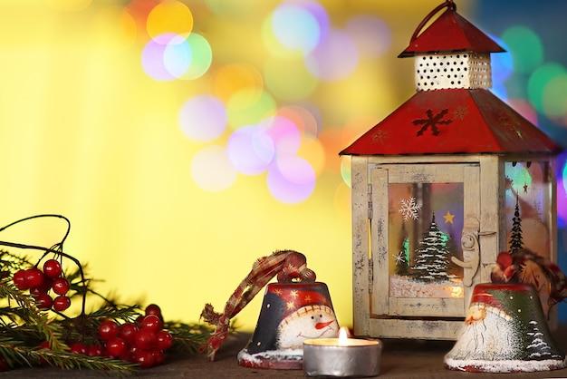 Елочные украшения со свечами под; цветной размытый фон.