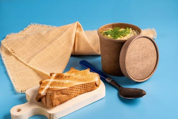 持ち帰り用の紙製使い捨てカップのチキンスープとパン