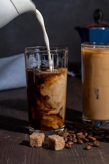 Сливки наливают в стакан с кофе со льдом, на деревянный стол с кофейными зернами и сахаром.