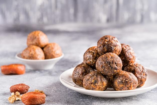 Фруктовые и ореховые энергетические шарики в тарелке, вид спереди.