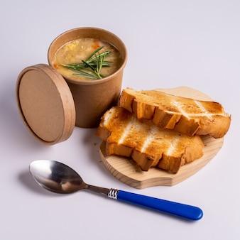 紙の使い捨てカップにエンドウ豆のスープ、テイクアウト、または青色の背景にパンと食品の配達