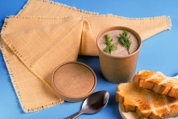 持ち帰り用の紙製使い捨てカップと自家製パンのキノコのスープ