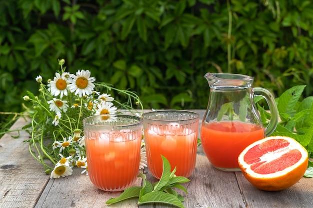 Грейпфрутовый сок с кубиками льда, листьями мяты и букетом ромашек