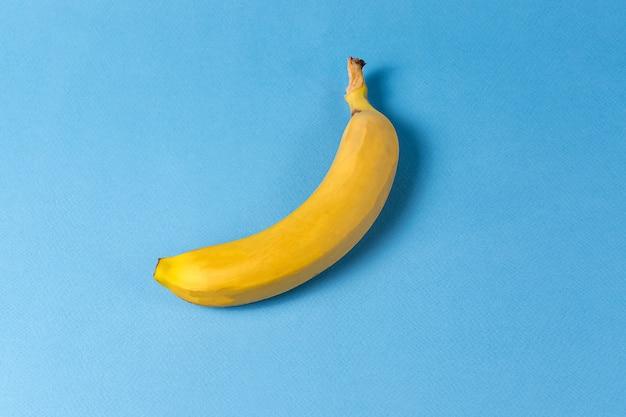 ミニマリズムスタイル。青い背景上の黄色のバナナとフルーツのパターン。