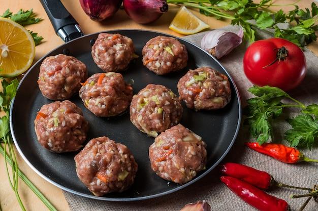 野菜と一緒に、調理する前に、鍋に自家製生のミートボール