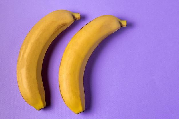 ミニマルスタイル。紫色の背景の上に黄色の熟したバナナ果物とフルーツパターン。