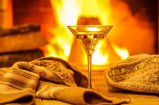 居心地の良い暖炉の背景に対してマティーニのグラス