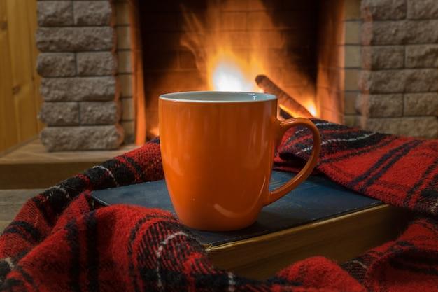 お茶、本、ウールのスカーフとオレンジマグカップと暖炉の前に居心地の良いシーン。