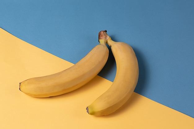 ミニマルスタイル。黄色と青の背景の上に黄色の熟したバナナ果物とフルーツパターン。