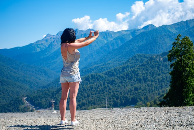 少女はスマートフォンで山の風景を写真します。