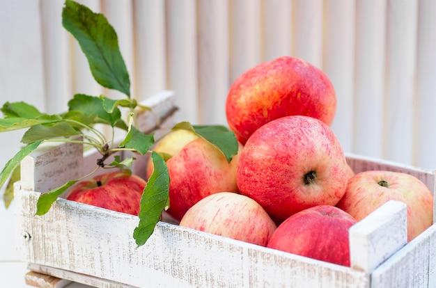 白い背景の上の木箱で新鮮でおいしい赤いリンゴ