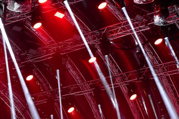 プロジェクタースクリーンの上の暗い背景にコンサートの照明からの光線。