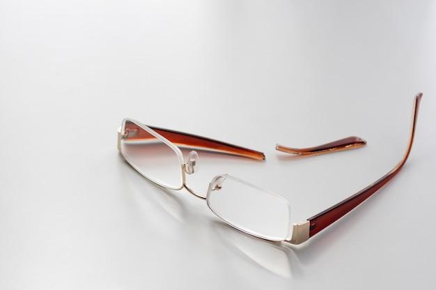 白い背景の上の割れたメガネ。メガネの耳当てが折れています。