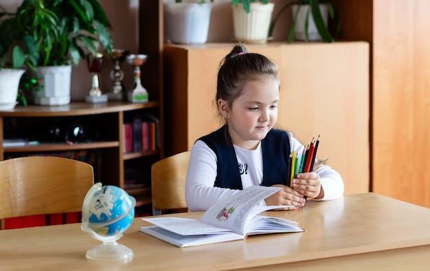 Маленькая школьница сидит за партой и держит в руках карандаши.