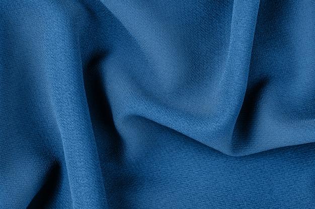 Монохромная декоративная ткань синего цвета. тенденция тени. тканевый фон. вид сверху. копировать пространство