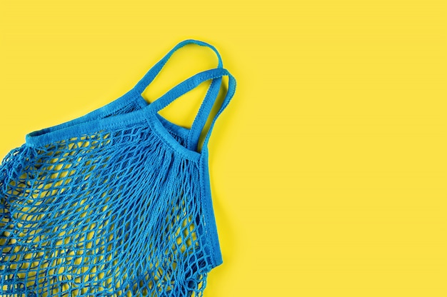 Синяя многоразовая сетка на желтом фоне. экологическая концепция. забота об окружающей среде и отказ от пластика.