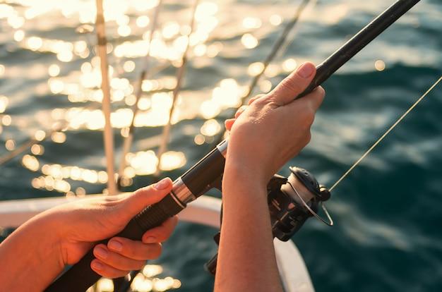 海の背景に対して釣り竿を持っている女性の手。女性は釣りです。