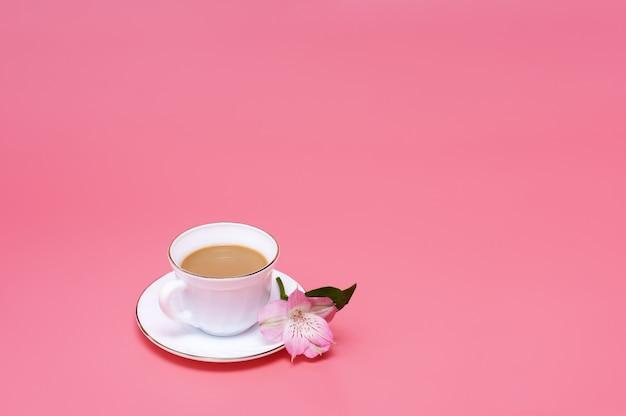 Стиль минимализм. одна чашка кофе с молоком на розовом фоне.