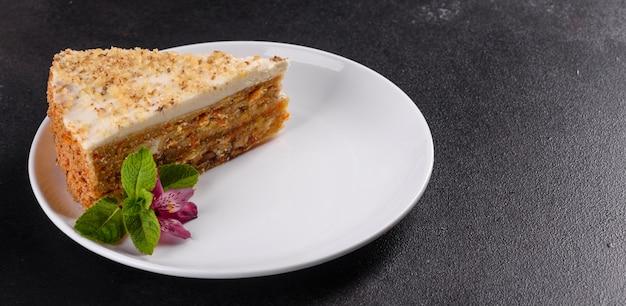 Свежий вкусный морковный пирог с кремом на темном фоне. морковный пирог с взбитой глазурью
