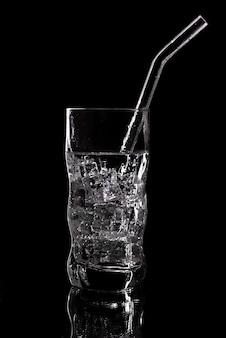黒い背景に氷と炭酸水炭酸飲料のガラス。黒い背景にガラスに澄んだ水を注ぐ