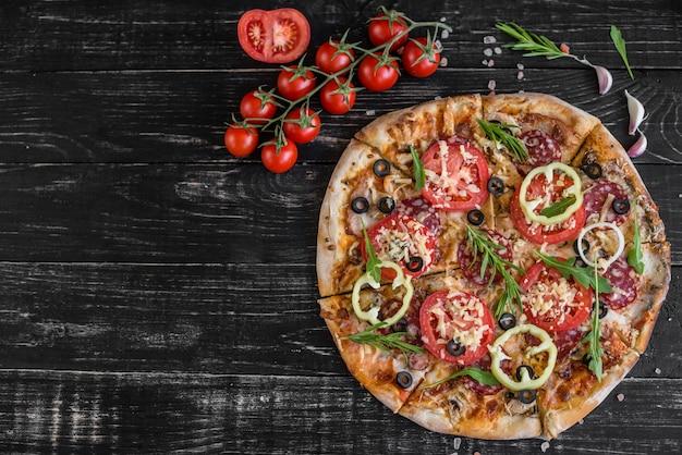 黒い木製の背景に野菜、きのこ、トマトのピザ。背景として使用することができます