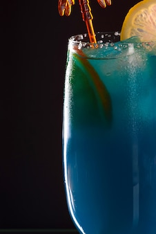 バーカウンターでさわやかなクールなブルーキュラソー。パーティーでカクテル。バーでの夜のご滞在
