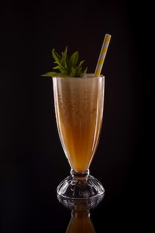 Холодный освежающий лед папайи свежий с коктейльной трубкой на черном фоне