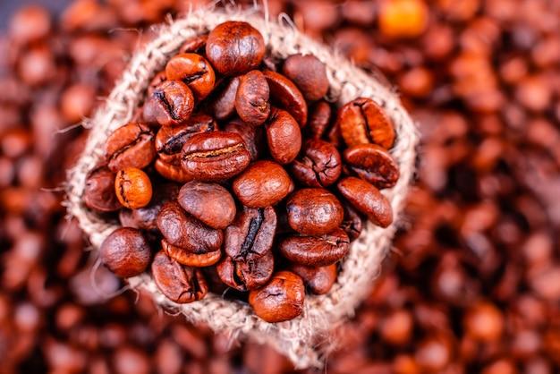 Семена ароматного кофе на темном фоне бетона. может использоваться как фон