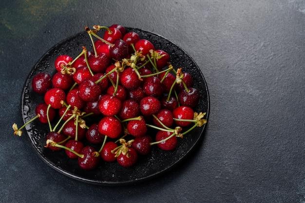 茎と葉と熟したチェリーの山のクローズアップ。新鮮な赤いサクランボの大規模なコレクション。