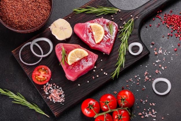 黒い表面にスパイスとハーブが入った新鮮なマグロの切り身ステーキ。マグロを焼くための準備