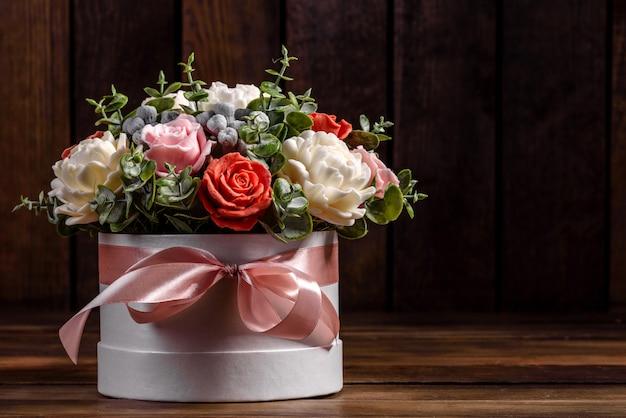 Букет красивых ярких розовых цветов в подарочной цилиндрической картонной коробке