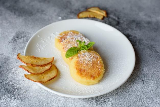 コンクリートの背景にミルクのガラスと白い皿においしい新鮮なカッテージチーズのパンケーキ。健康的でダイエットの朝食