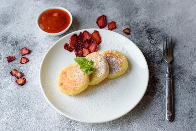 コンクリートの背景に白い皿の上のおいしい新鮮なカッテージチーズのパンケーキ。健康的でダイエットの朝食